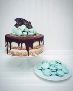 Chocolate dripped cake with geen macarons